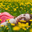 Beautiful girl lying on the field of dandelions — Stock Photo #28789357