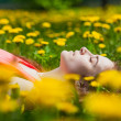 Beautiful girl lying on the field of dandelions — Stock Photo #28789361