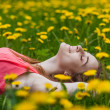 Beautiful girl lying on the field of dandelions — Stock Photo #28789611