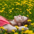 Beautiful girl lying on the field of dandelions — Stock Photo #28789753