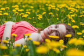 Beautiful girl lying on the field of dandelions — Stock Photo