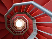 Spiral staircase of iron covered with a red carpet — Stock Photo