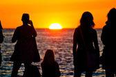 Women silhouette watching sunset on sea coast — Stock Photo