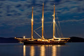 Wooden sailboat illuminated at night — Stock Photo