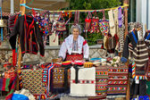 Lady in traditional clothes selling on booth — Stock Photo