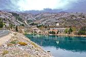 Old stone fishermen village under mountain — Stock Photo