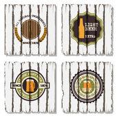 Quatro rótulos de cerveja no fundo de madeira velho — Vetorial Stock
