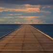 Old wood bridge to the sea with cloudy sky — Stock Photo