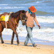 Cowboy walking with his horse on the sea beach — Stock Photo