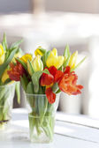 Yellow and blssom tulip flower in a glass decorated on white table — Stock Photo