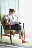 Asian girl reading while sitting in an easy chair — Stock Photo