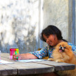 Girl sitting and painting in home with pomeranian dog — Stock Photo