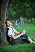 Woman sitting in the green garden with bicycle — Stock Photo