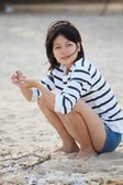Teen woman sitting on the beach and sea shell in her hand — Photo