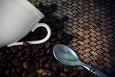 белый кубок и кофе в зернах жареный на деревянный стол — Стоковое фото