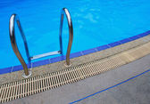 Swimming pool handle with blue water — Stock Photo