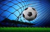 Soccer football in goal net and stadium blue sky background — Stock Photo