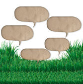 Speech bubbles over green grass field — Stock Photo
