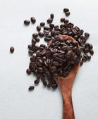 Coffee bean seeds on wood spoon — Stock Photo