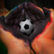 Soccer football in painting hands — Stock Photo