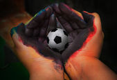 Soccer football in painting hands — ストック写真