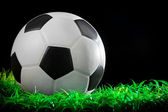 Soccer football on green grass by studio light — Stock Photo
