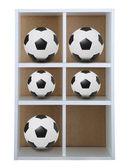 Soccer footballs on shelf — Stock Photo