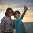 Two Asian women are photographed on a background of the sea — Stock Photo #19200949