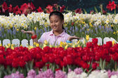 Asian girl standing in the garden of tulips with smiling face — Stock Photo