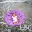 Baby sitting on round chairs at sea beach — Stock Photo