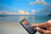 Sea scene in mobile phone and finger press ok — Stock Photo