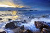 Sunset on rock beach — Stock Photo