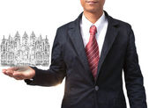 Business man holding drawing of modern building — Stock Photo
