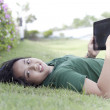 Girl and tablet computer on green grass - Stock Photo