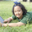 Girl lying on green grass with computer tablet in hand - Stock Photo