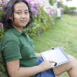 Girl sittingon green grass with computer tablet in hand - Stock Photo