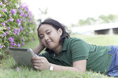 Girl and tablet computer lying on green grass field — Stock Photo