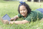 Girl lying on green grass with computer tablet in hand — Stock Photo