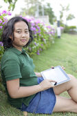 Girl sittingon green grass with computer tablet in hand — Stockfoto