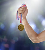 Hand and gold mmedal — Stock Photo
