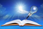 Ouvrir le livre sur la mer et le ciel bleu avec ampoule crayon — Photo