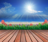 Wood terrace and flowers garden with blue sky and sunshine above — Stock Photo