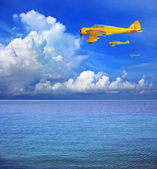 Three of yellow plane flying over sea water — Stock Photo