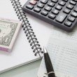 Stack of bank note and pen calculator on note book  — Stockfoto