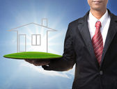 Business man holding new home on empty land for sale — Stock Photo