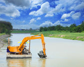 Heavy machine working in canal — Stockfoto