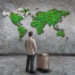 Young man standing and looking to green world map on cement wall with big suitcase use for people traveling theme — Stock Photo #29881335