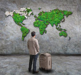 Young man standing and looking to green world map on cement wall with big suitcase use for people traveling theme — Stock Photo