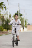 Girl riding bicycle in village park — Stock Photo