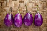 Purple eggplant on bamboo craft — Stock Photo